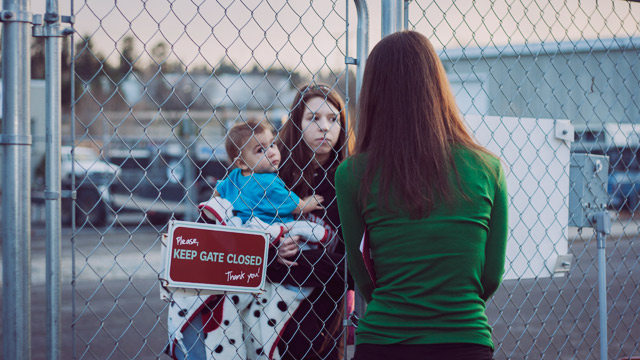 woman with child standing at shelter gate