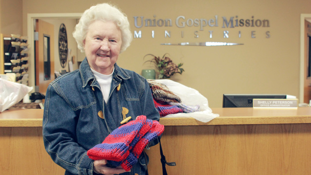 Lady donating knitted hats