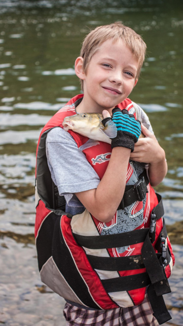 smiling boy holding close a fish he caught