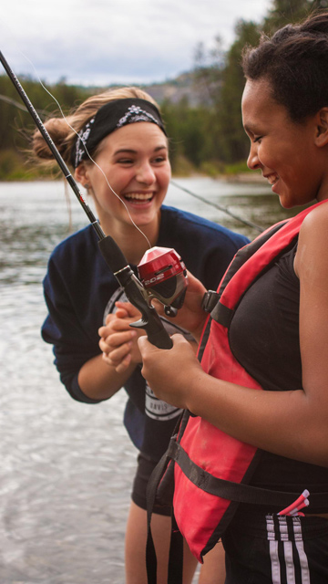 counselor laughing and fishing with young girl
