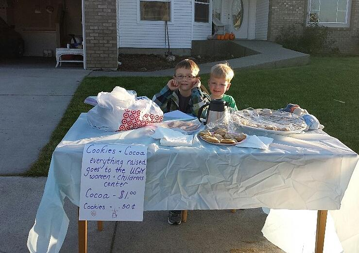 child sells cocoa and cookies for poor