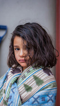 Little girl wrapped in blanket at shelter