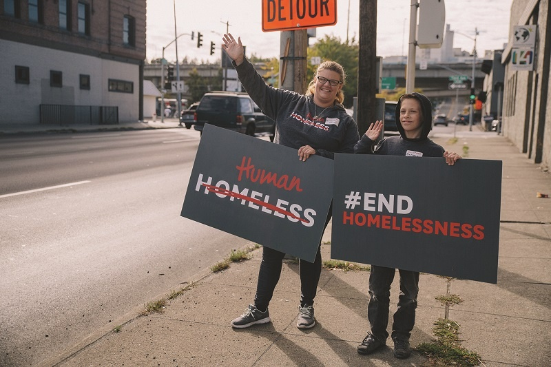 Barbara and Damyen waved signs as part of World Homeless Day 2018.
