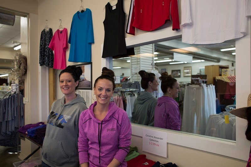 Lacey and Tiffany put out clothing for sale at the UGM Thrift Store