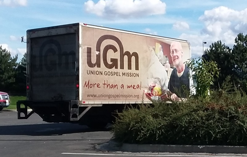 Paul is on the side of the truck Larry drives to pick up donations from UGM's food partners.