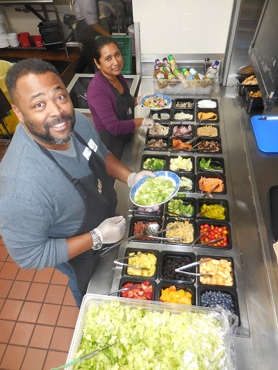 Volunteers help feed the hungry at the salad bar.