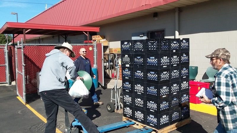 Blake and others on the warehouse crew help move the milk donations into the refrigerators after it was donated by Darigold, one of UGM's food partners.