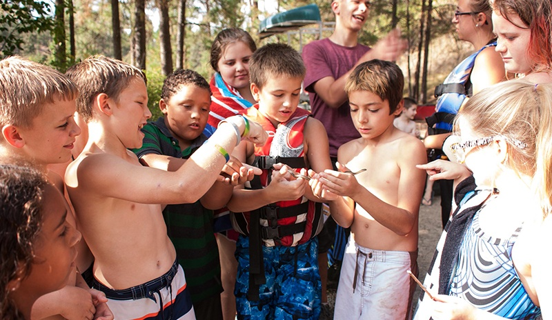 Campers gather around a small snake they found at UGM Camp. Getting away from the city and close to nature is an important part of the camp experience.