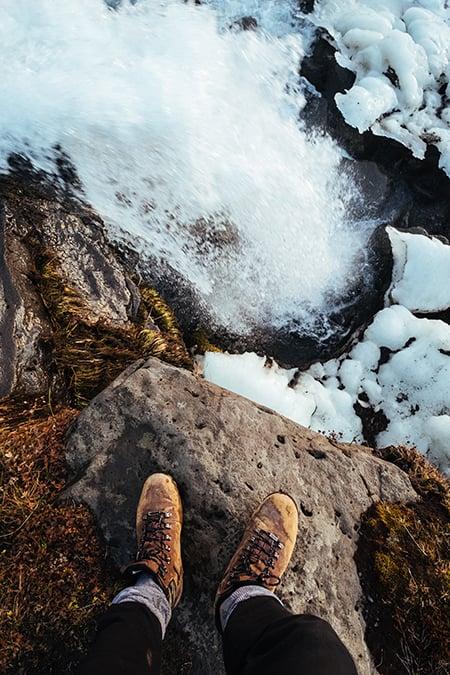 feet on rock by water
